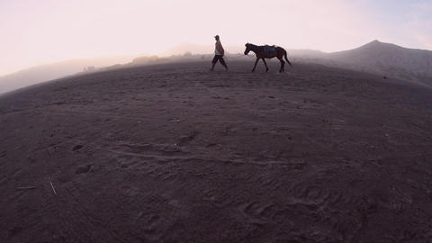 Horseman walking with his horse in the morning near Mount Bromo, Indonesia Footage