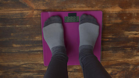 Female feet standing on weight scales Live Action