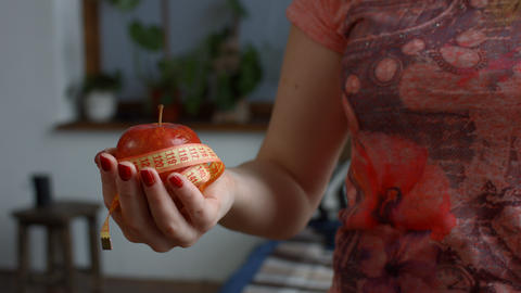 Woman holding fresh apple and measure tape Live Action