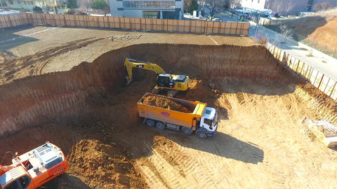 Aerial shot of excavators and tipper tracks working at construction Footage