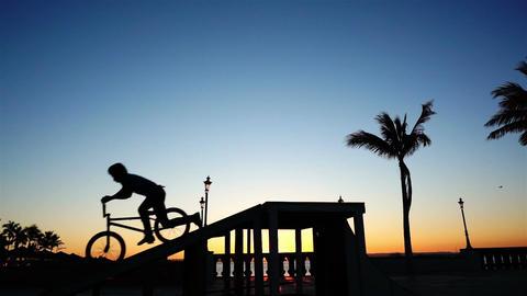 BMX Biker Silhouette Doing a No Hands Jump Stock Video Footage