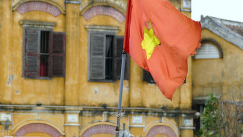 Vietnamese flag with old town buildings at the background Footage