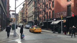 Yellow taxi cab and pedestrians on cobblestone street in Soho Footage