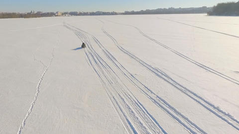 Winter fun. A trip on a snowmobile. Two guys are riding a snowmobile over frozen Footage