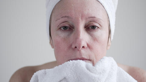 Middle-aged Caucasian Woman Applying Cosmetic Cream On Face.