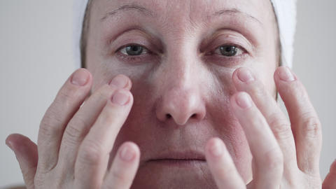 Middle-aged Caucasian Woman Applying Cosmetic Cream On Face. 0