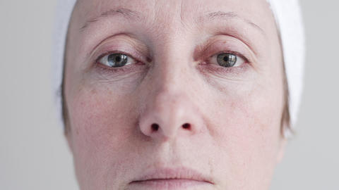 Middle-aged Caucasian Woman Applying Cosmetic Cream On Face. 1