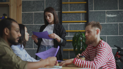 Young woman sharing documents with coworkers having start-up presentation in Live Action