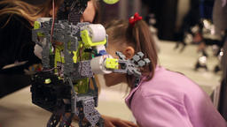 A little girl and a woman are talking to a robot. Modern robotic technologies Footage