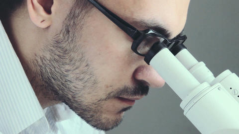 Young male doctor viewing through microscope Footage