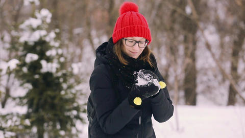 Beautiful young girl with glasses and a red knitted hat throws a snowball into Footage