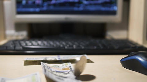 Bitcoin is spinning and Dollars bills falling near computer Footage