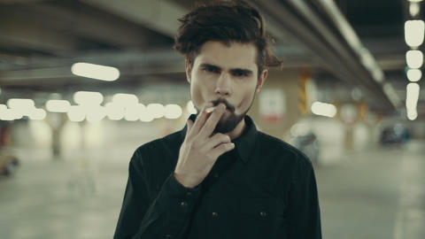 young handsome bearded man smoking cigarette Live Action