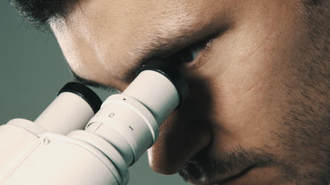 Young scientist looking through the microscope Footage