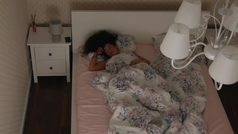 Girl restlessly sleeps on the bed at night Top view Footage