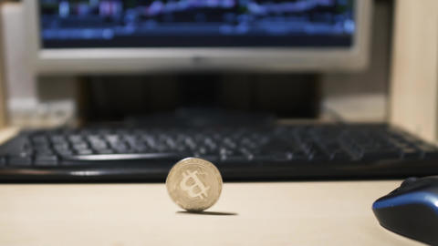 Bitcoin is spinning against the background of a monitor and keyboard Footage