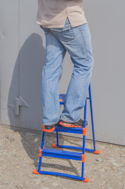 The man in the blue jeans standing on a ladder outdoors Photo