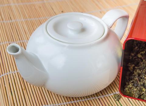 Teapot and a tin of traditional Asian green tea loose Photo