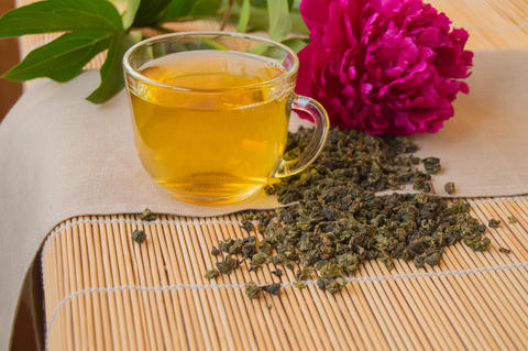 Cup of green tea, the leaves loose and peony flower Photo