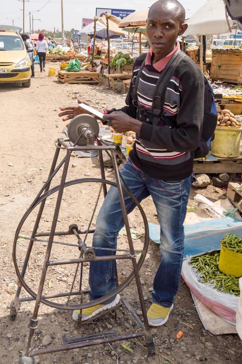 Knife sharpener on a Nairobi suburb market in Kenya Photo