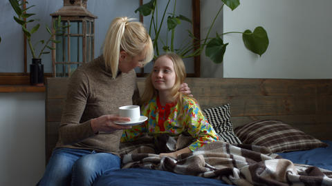 Caring mother giving her ill daughter hot tea Footage
