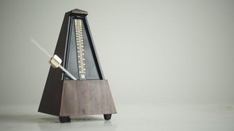 Vintage metronome with golden pendulum beats slow rhythm Live Action