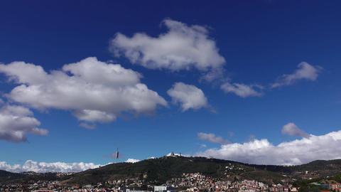 Light cumulus cloud at deep blue sky over Tibidabo mountain, time lapse shot Footage