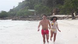 Couple Running Through Waves On Beach Footage
