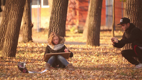 the girl sitting on the ground in the Park and draws autumn landscape Footage