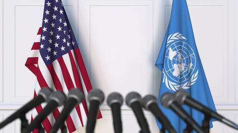 Flags of the USA and the United Nations at international meeting or negotiations Footage