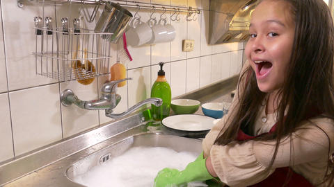 Young girl washing dishes with crazy happy smile Footage