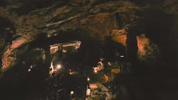 Large group of adult tourists exploring the Saeva Cave in Bulgaria going down Image