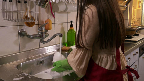 Young girl washing dishes tilt up look ar camera Footage