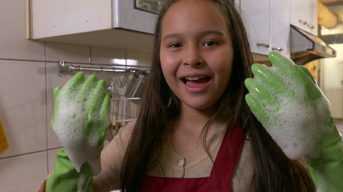 Young girl washing dishes showing foamy hands CU tilt Footage
