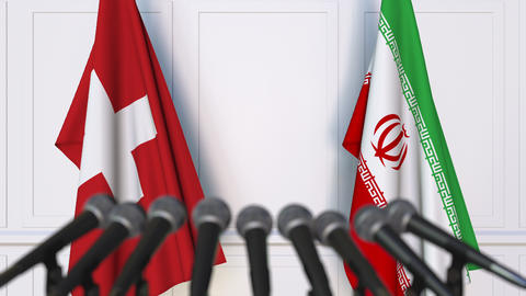 Flags of Switzerland and Iran at international meeting or negotiations press Footage