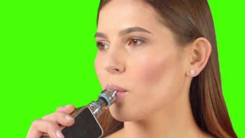 Girl with a vaporizer on a on a green background vaping e-cigarette Live Action