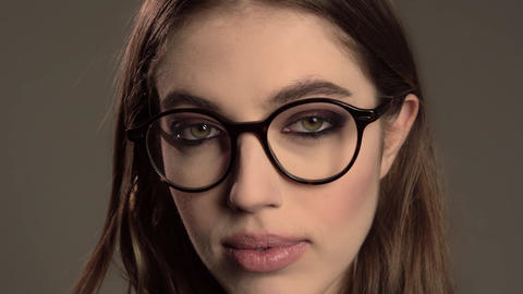 Indoor portrait of young good-looking girl in round glasses on gray background Footage