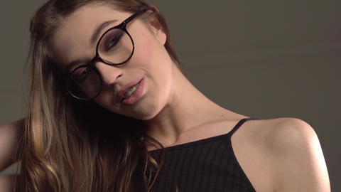 Indoor portrait of young good-looking girl in round glasses with braces on gray Footage