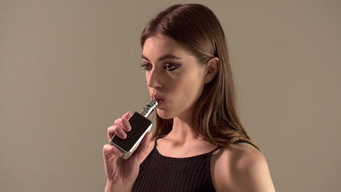 Girl with a vaporizer on a gray background vaping e-cigarette Live Action