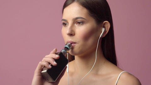 Young woman listening music and smoking vaporizer Live Action