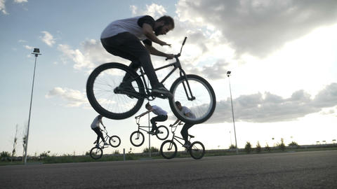 Amazing slow motion with cool teenagers riding on bicyclers and practicing Footage