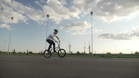 Extreme young biker performing jumps and rotation maneuvers exercising ollie Footage