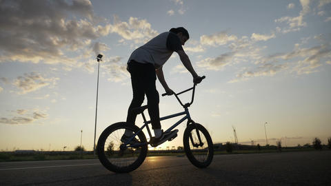 Professional young bicycler jumping on his bike rotating the handlebar in midair Footage