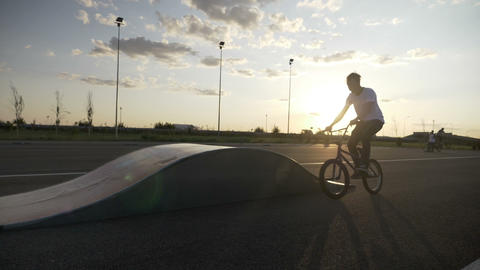 Young male biker riding on the edge of ramp in an acrobatic training at sunset Footage