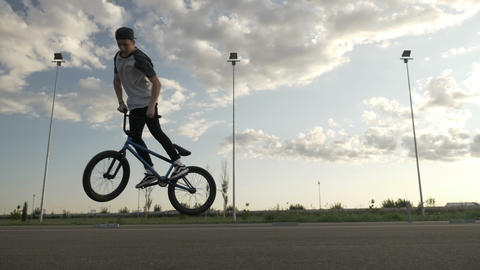 Slow motion of talented athletic bicycler exercising a mid air rotation jump on Footage