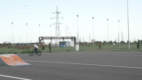 Young biker pedaling over a ramp in a recreational area Footage