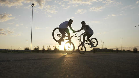 Couple of teen bikers doing high five while performing an amazing front wheelie Footage
