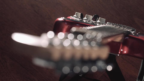 Guitar on stage, natural flare flashing as lights move, focus on body Footage