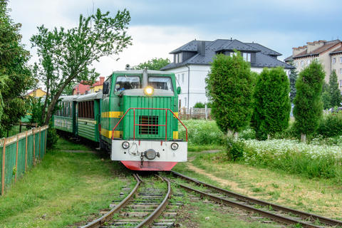 The train rides a narrow path and carries tourists in the Carpathians フォト