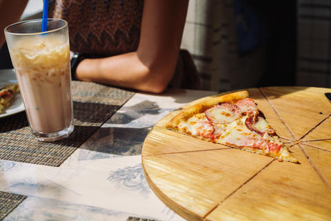Unrecognizable woman eating pizza in cafe Photo